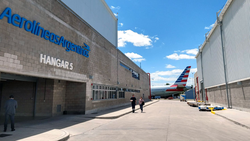 Puerta de entrada al hangar 5 de Ezeiza. Al fondo, estacionado, un Boeing 777 de American Airlines.