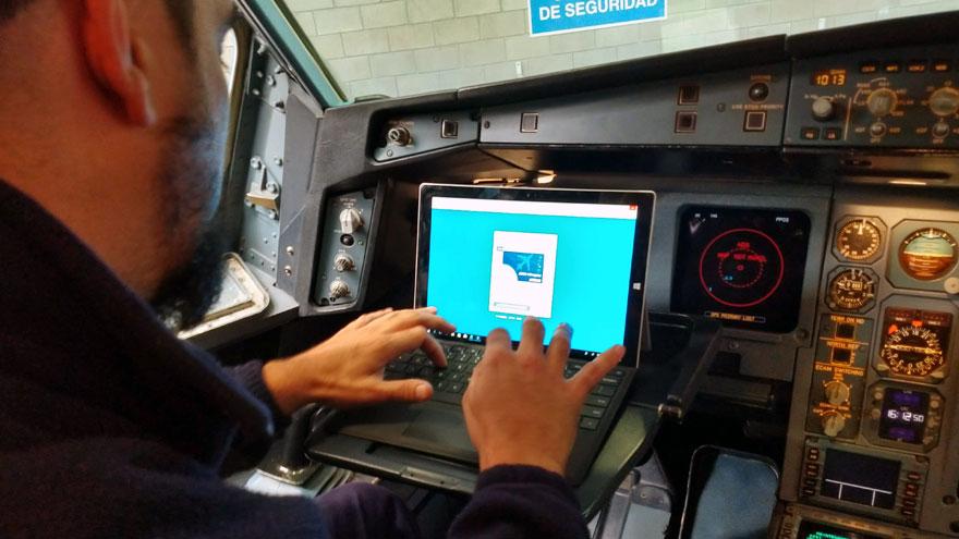 Un técnico ingresa al software AMOS en una tableta Surface en la cabina de vuelo del Airbus A340-300B LV-FPU.